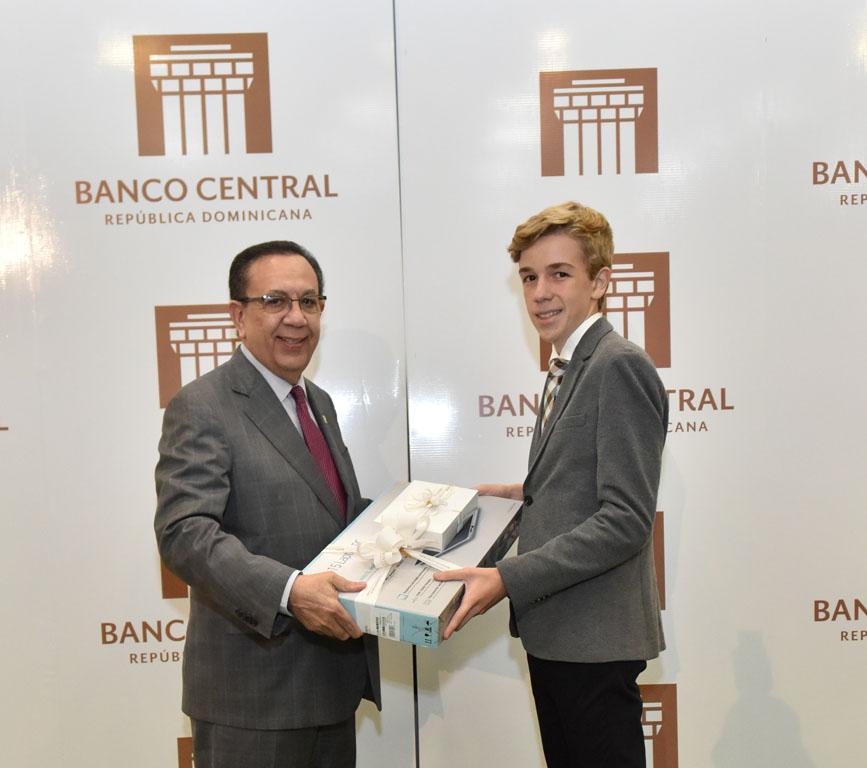 El gobernador del BCRD, Héctor Valdez Albizu, le entrega un premio al joven meritorio Manuel Actis Cassa.