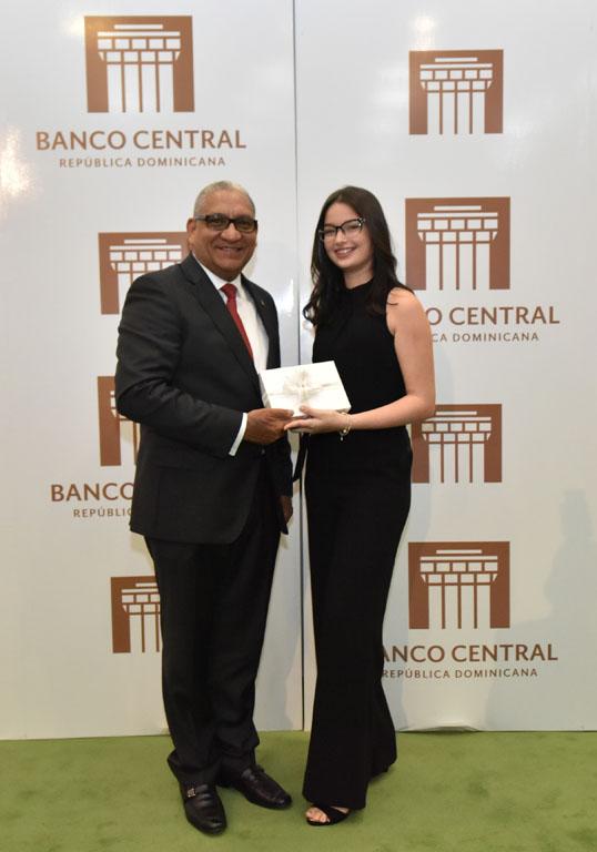 El gerente del BCRD, Ervin Novas Bello, le entrega a la estudiante María Gabriela Nadal Montero.