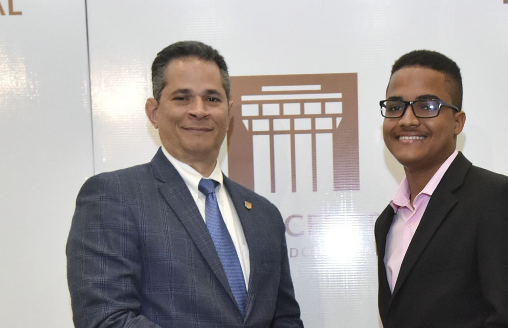 Joel Tejeda, subgerente de Políticas, le entrega su premio a Yefri Fabián Rodríguez Abreu.
